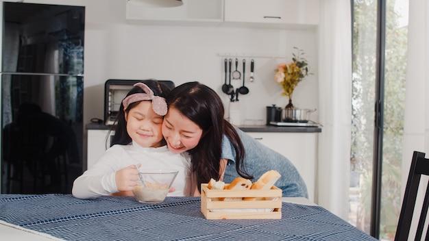 La famiglia giapponese asiatica fa colazione a casa. la mamma e la figlia asiatiche che si sentono felici parlano insieme mentre mangiano il pane, il cereale dei fiocchi di mais e il latte in ciotola sulla tavola in cucina moderna a casa nella mattina.