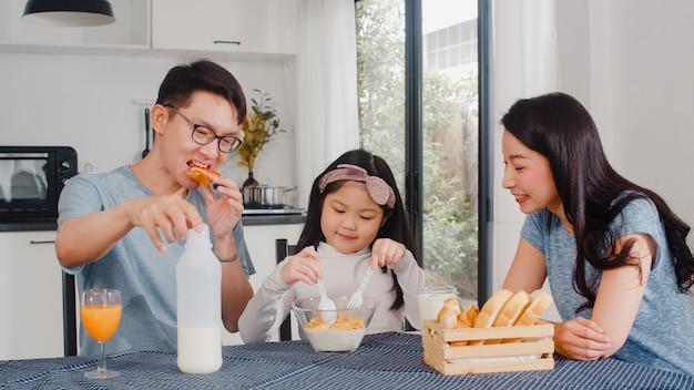 La famiglia giapponese asiatica fa colazione a casa. la mamma, il papà e la figlia asiatici che si sentono felici parlano insieme mentre mangiano il pane, i cereali dei fiocchi di mais e il latte in ciotola sulla tavola nella cucina di mattina.