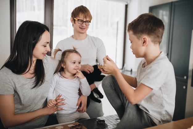 La famiglia prepara i biscotti di pan di zenzero in cucina. papà, mamma, figlio, figlia, fratello e sorella. impastare, tagliabiscotti, capodanno, natale, cena festiva. abbigliamento per la casa grigio.