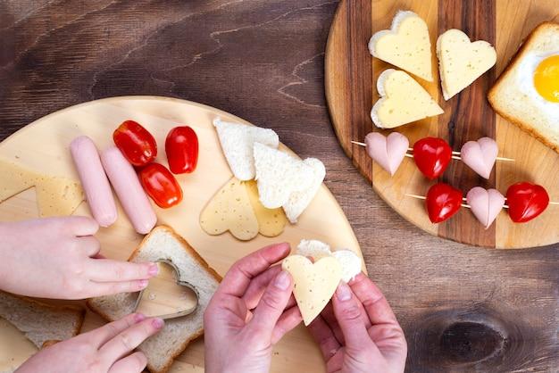 La famiglia prepara il cibo a forma di cuore