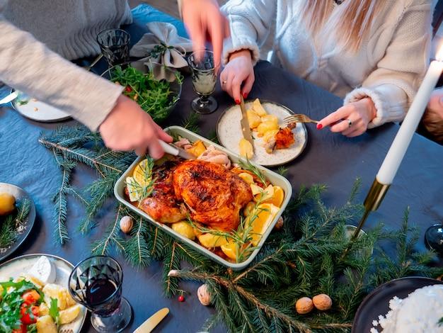 La famiglia si siede al tavolo di natale pieno di cibo