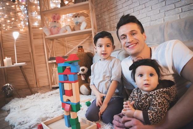 La famiglia sta giocando con i cubi per i bambini di notte a casa.