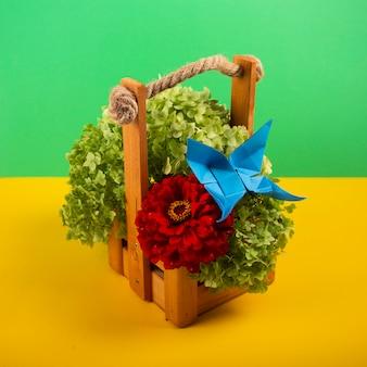La farfalla di origami su un cespuglio verde in un canestro su un fondo colorato bello colpo dello studio del mazzo ha sparato su giallo