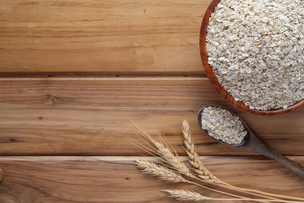 La farina d'avena è posizionata su un legno marrone.