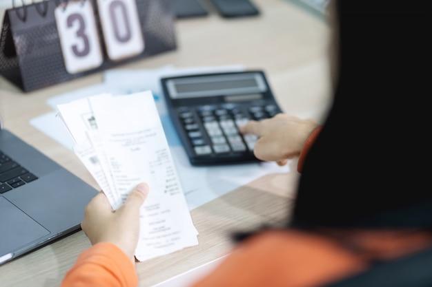 La fattura della tenuta della donna e il calcolatore usando e calcolano la fattura e il pagamento di costo.