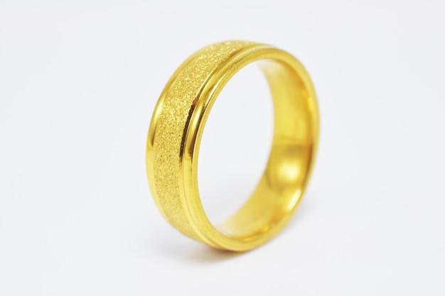 La fede nuziale dorata su superficie bianca, coppia l'amore si sposa