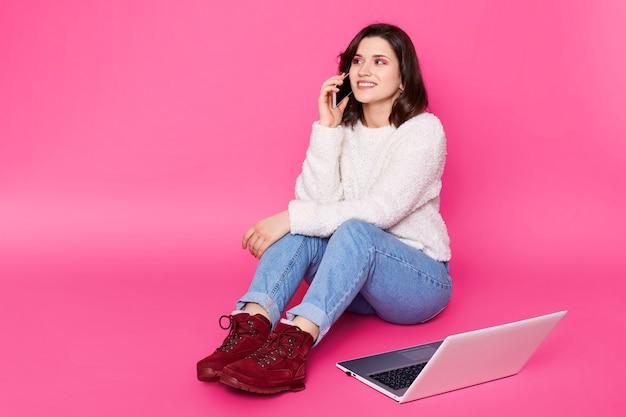 La femmina attraente con il bello sorriso si siede sul pavimento a casa