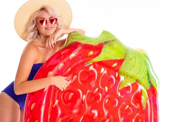 La femmina caucasica bionda graziosa si leva in piedi in costume da bagno con il materasso di gomma e i sorrisi della spiaggia isolati su priorità bassa bianca