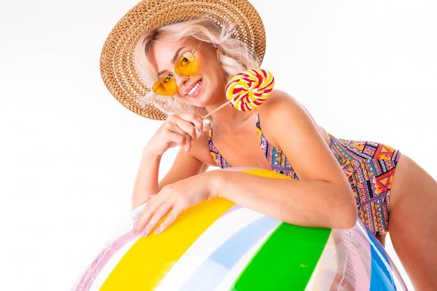 La femmina caucasica bionda graziosa si leva in piedi in costume da bagno con la sfera variopinta, il lolipop e i sorrisi della grande spiaggia di gomma isolati