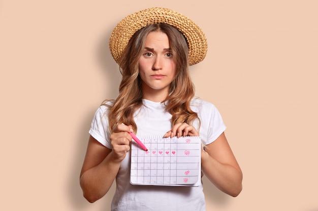 La femmina caucasica dispiaciuta in maglietta e cappello di paglia casuali, indica al calendario di periodo, non vuole avere le mestruazioni durante il riposo in riva al mare, isolata sul beige. donna infelice coperta