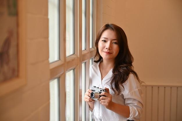 La femmina che tiene la retro macchina fotografica d'annata.