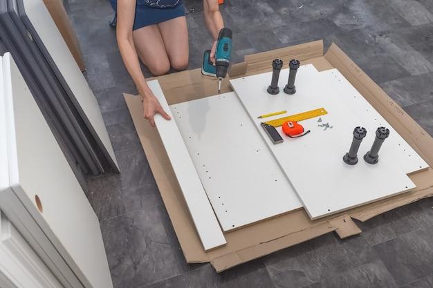 La femmina con autista cordless raccoglie mobili. vista dall'alto.
