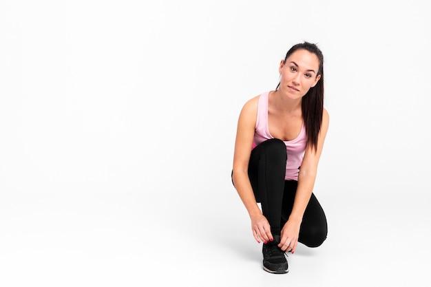 La femmina copia-spazio lega i lacci delle scarpe