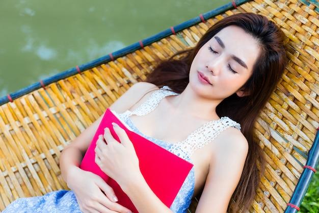 La femmina dell'adolescente che si trova sull'amaca di bambù e ha letto un libro
