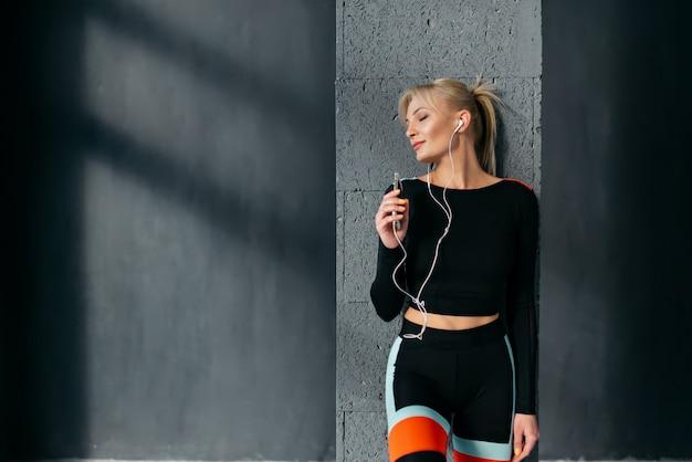 La femmina di sport ascolta musica in cuffia con gli occhi chiusi