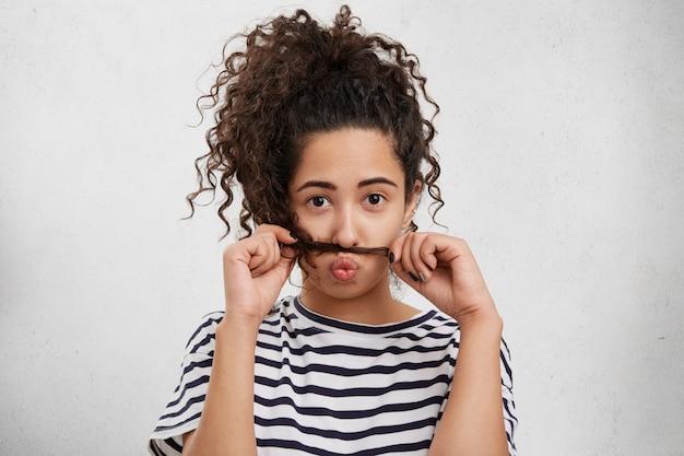 La femmina divertente mette il broncio sulle labbra, mette la serratura sotto il naso, si sente annoiata mentre aspetta qualcuno.
