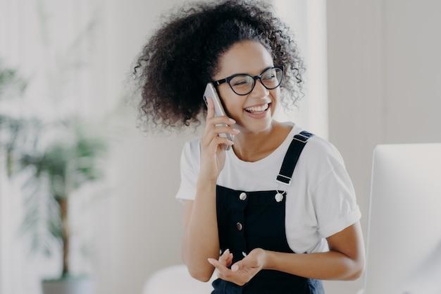 La femmina estatica discute qualcosa di piacevole tramite il telefono cellulare