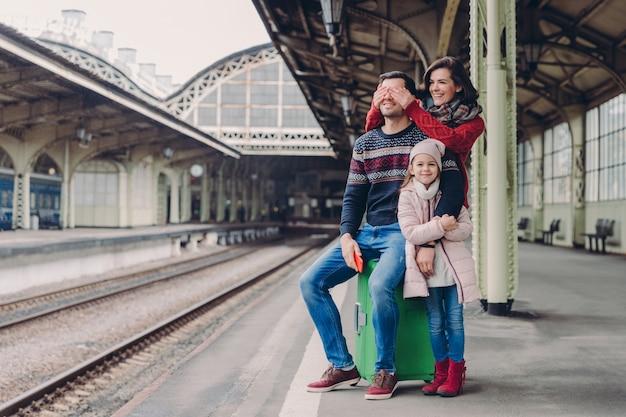 La femmina felice copre gli occhi di suo marito, fa sorpresa. la famiglia amichevole di madre, padre e figlia stanno insieme alla stazione ferroviaria, si divertono mentre aspettano il trasporto.