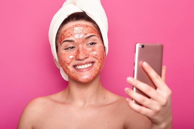 La femmina felice felice con pelle molle fa il selfie mentre solleva la procedura della stazione termale, indossa l'asciugamano bianco, ha lo sguardo felice, posa sorridere isolato sul rosa. concetto di persone, bellezza e cura della pelle