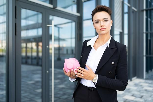 La femmina in vestito dell'ufficio ha preso un appuntamento e sta aspettando il collega con salvadanaio