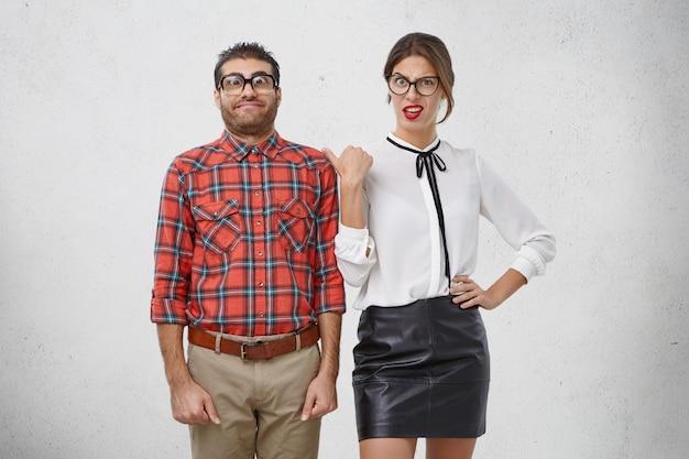 La femmina infastidita indica il nerd maschio, si sente annoiata e irritata con lui