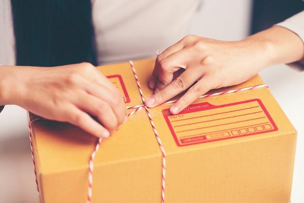 La femmina passa il contenitore di imballaggio al magazzino, concetto online di vendita