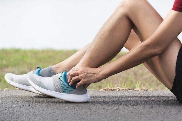 La femmina si aggrappa a una brutta gamba. il dolore alla gamba. salute e concetto doloroso.