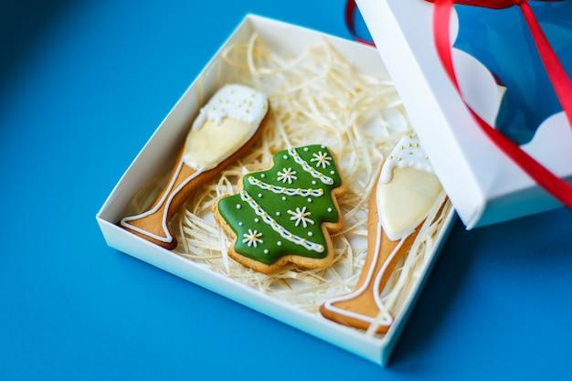 La festa del nuovo anno di natale, i vetri di campagne e il pan di zenzero dell'albero di natale hanno imballato in scatola sul concetto blu di festa del fondo.