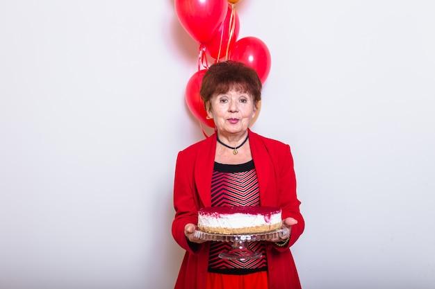La festa di compleanno senior della tenuta della donna balloons su un fondo bianco