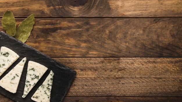 La fetta di formaggio blu si sistema su un'ardesia nera con foglie di alloro su una vecchia scrivania di legno