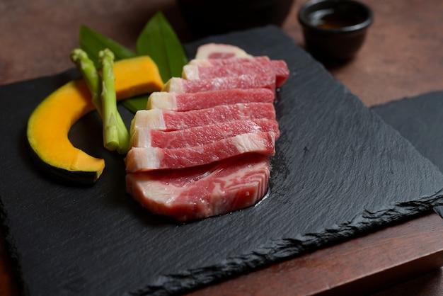 La fetta di petto di manzo crudo fresco con pezzi di zucca e asparagi sulla roccia di piatto nero, set di menu.