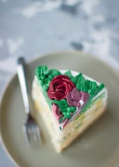 La fetta di torta della ragazza lattea ha decorato le foglie verdi ed i fiori del giglio, la torta decorata come mazzo del fiore, decorazione del dolce della molla