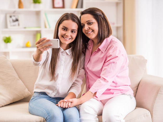 La figlia con la mamma fa un selfie nella stanza.
