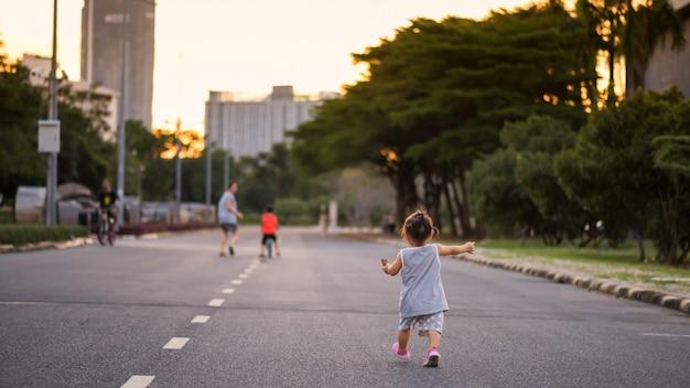La figlia corre seguendo mamma e fratello