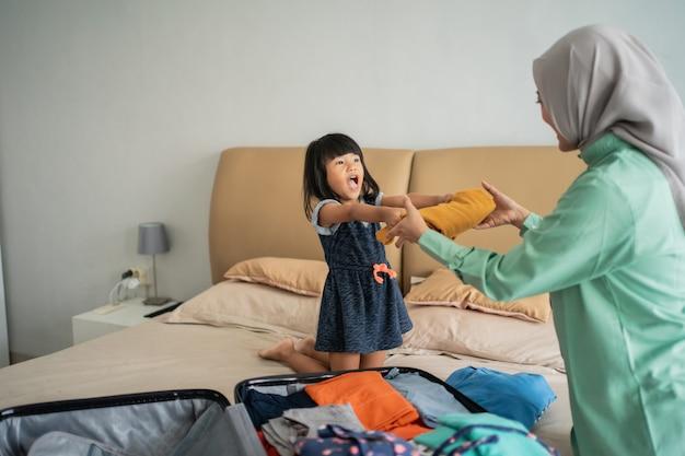 La figlia dà vestiti a sua madre che prepara la valigia