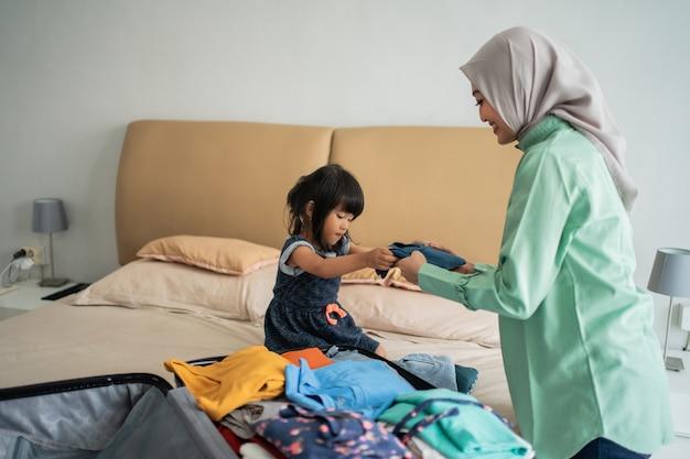 La figlia dà vestiti a sua madre per preparare la valigia