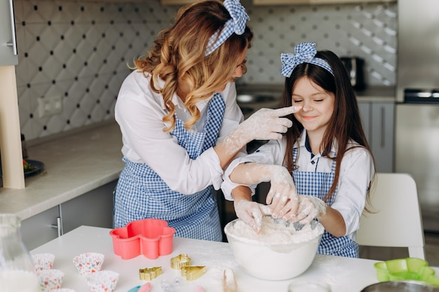 La figlia e sua madre in famiglia si divertono durante la cottura insieme.