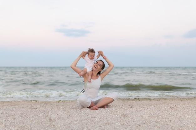 La figlia felice della madre e del bambino della famiglia che fa l'yoga, medita nella posizione di loto sulla spiaggia al tramonto