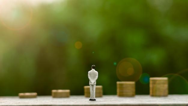 La figura miniatura dell'uomo d'affari che si leva in piedi per vede la parte anteriore anteriore monete dorate
