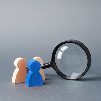 La figura umana di legno tre sta vicino ad una lente d'ingrandimento su un gray