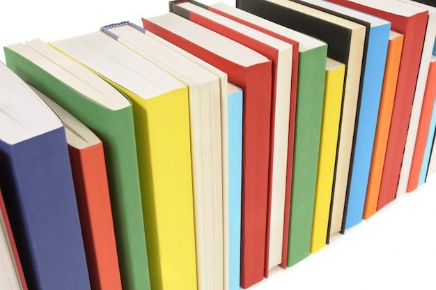 La fila dei libri variopinti ha impostato contro una priorità bassa bianca