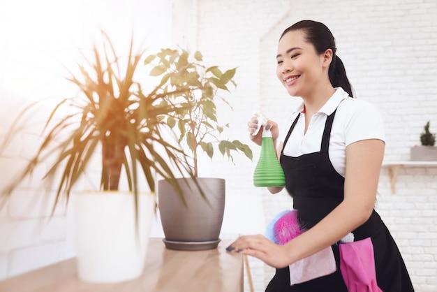 La filippina domestica che spruzza piante gode del lavoro.
