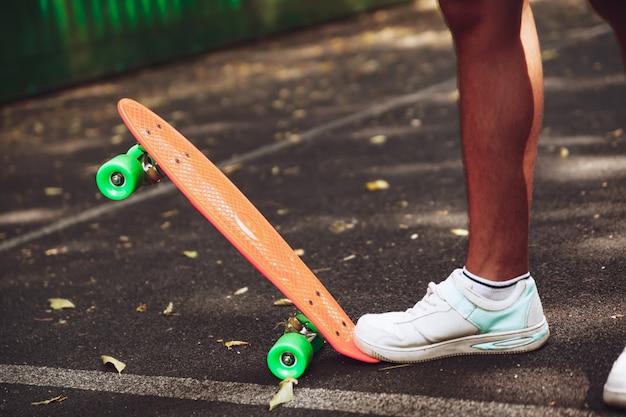La fine dei piedi delle scarpe da tennis dell'uomo guida sul pattino arancio del penny su asfalto