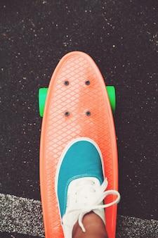 La fine dei piedi delle scarpe da tennis della ragazza guida sul pattino arancio del penny su asfalto