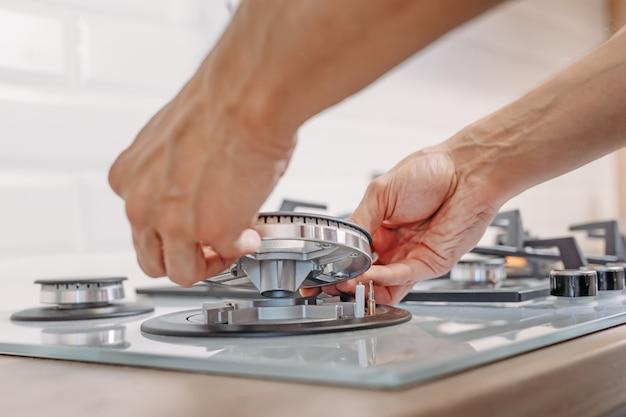 La fine della mano dell'uomo installa la fresa delle ongas del bruciatore in kithen. riparazioni del quadro di controllo del gas