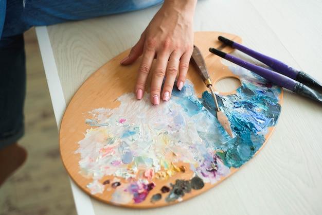 La fine della mano della donna mescola le pitture con la spazzola in tavolozza nella classe di arte