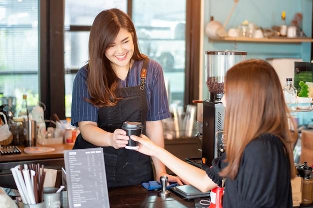 La fine della mano femminile sta prendendo il caffè caldo dal barista
