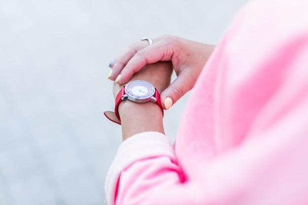 La fine della mano femminile tocca l'orologio sul polso sul pavimento della priorità bassa.