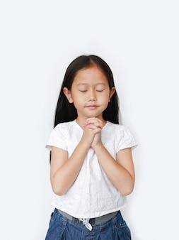 La fine osserva la bella piccola preghiera asiatica della ragazza del bambino isolata. spiritualità e religione.