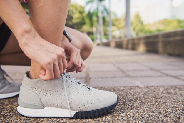 La fine su della giovane donna allaccia la sua scarpa pronta ad allenamento sull'esercitazione nel parco